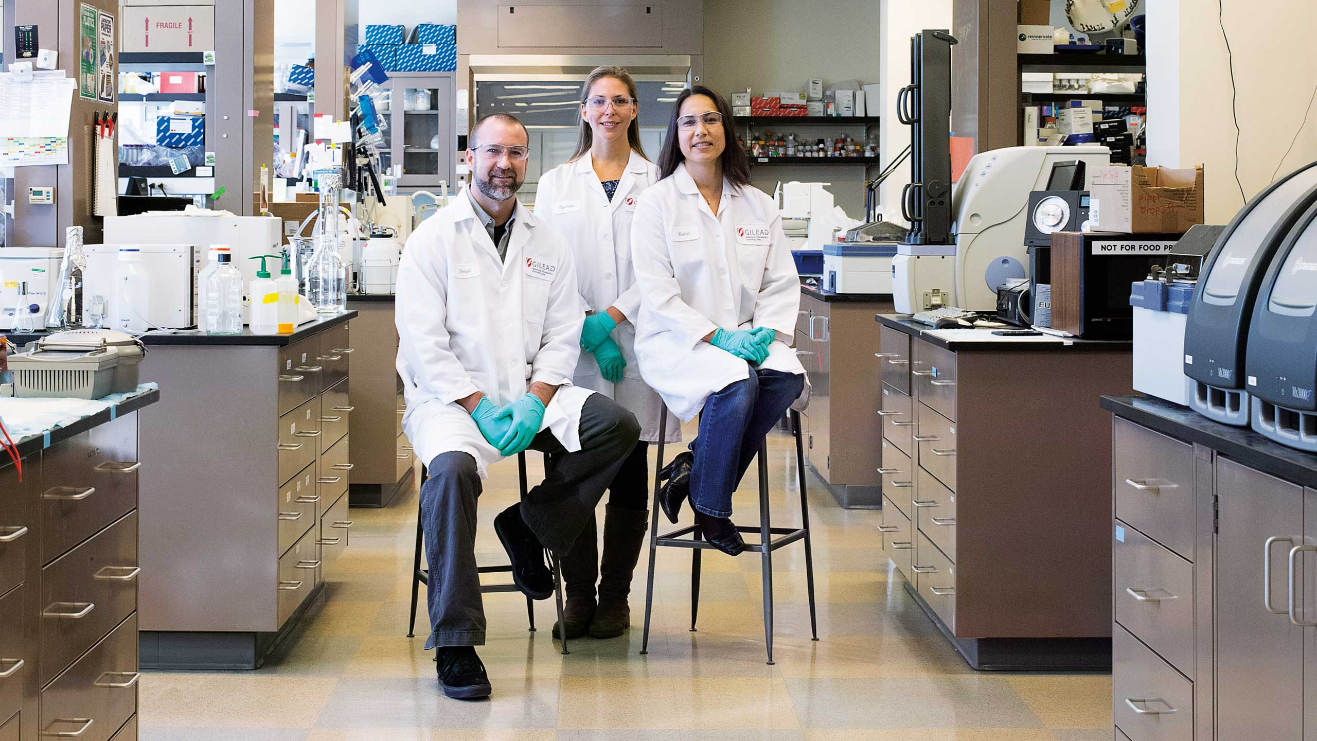 Gilead Brand Refresh Photograph of three scientists in a lab